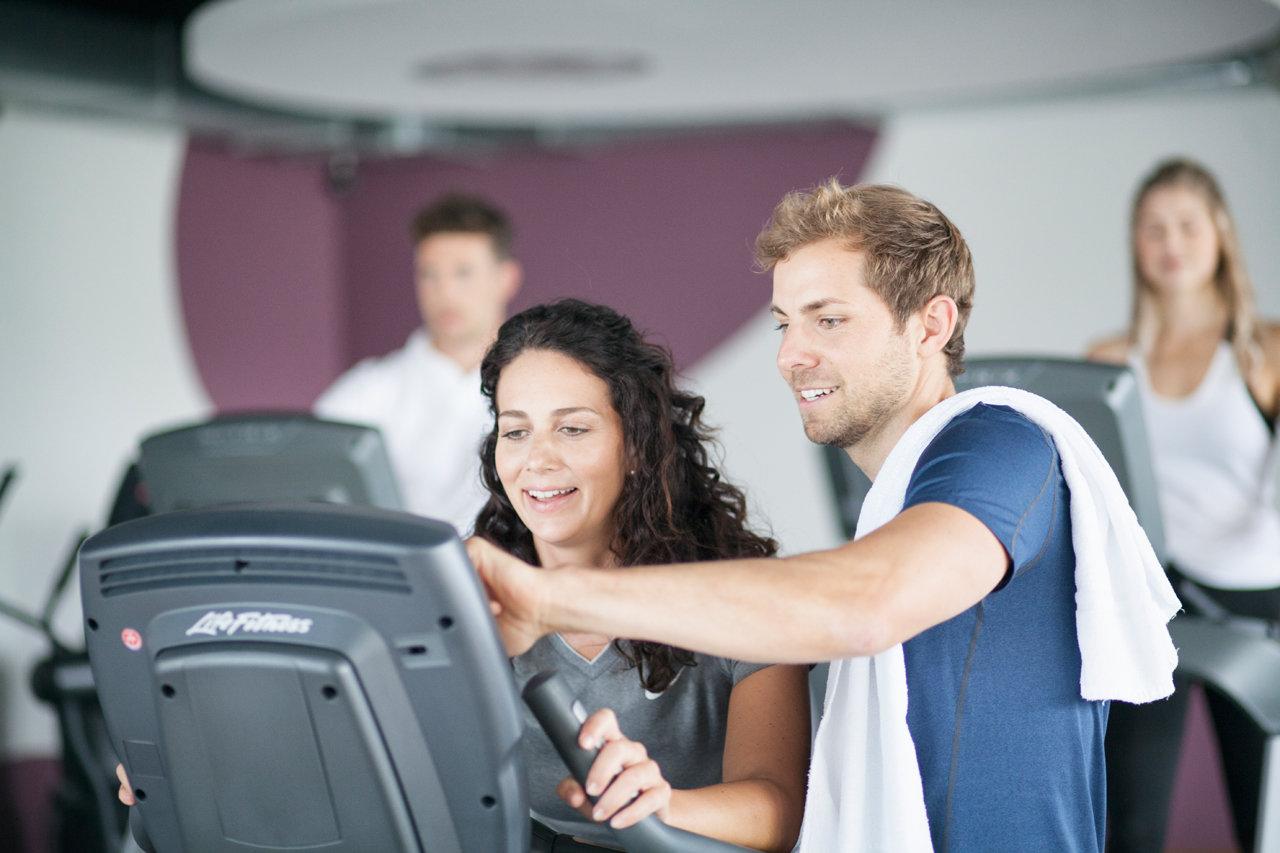 Fitnesstrainer erklärt Geräte im Studio