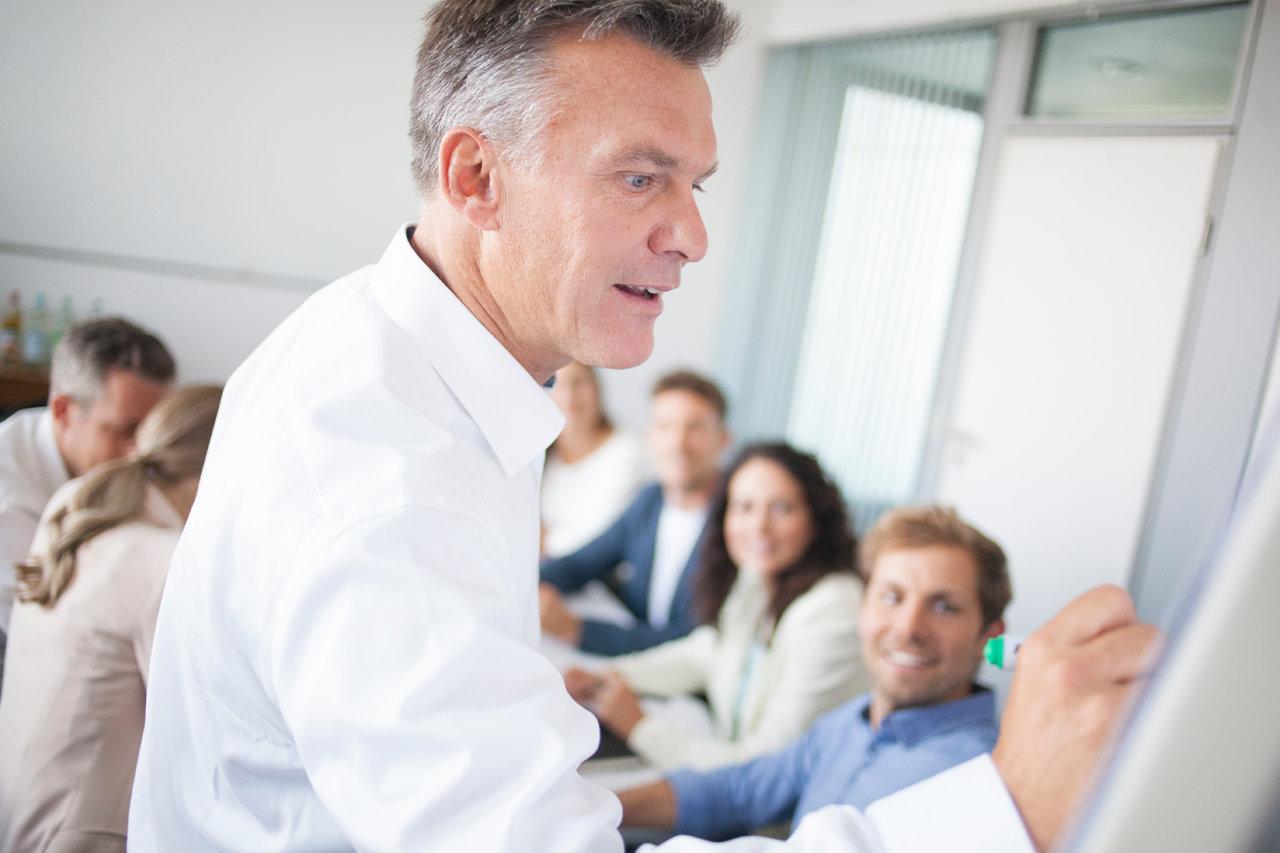 Mann an Flipchart im Beratungsgespräch mit mehreren Personen